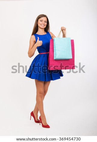 Smiling girl with the shopping bags showing the thumbs up - stock photo