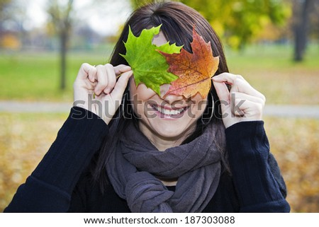 Smiling Girl with two colorful leaves - stock photo