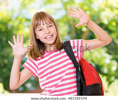 Smiling girl 10-11 year old stretching her hands up for greeting .Beautiful schoolgirl with backpack posing outdoors. Young student beginning of class after vacation.