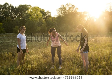Smiling girls doing yoga exercises outdoors at the park