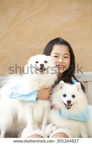 smiling girls embracing the two Spitz dogs