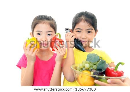 Smiling girls holding vegetables - stock photo