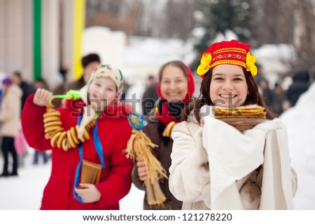 Smiling girls in russian traditional clothes with pancake during  Shrovetide