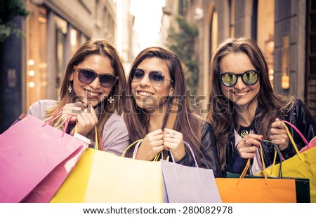 smiling girls with shopping bags. three friends making shopping in the city center - stock photo