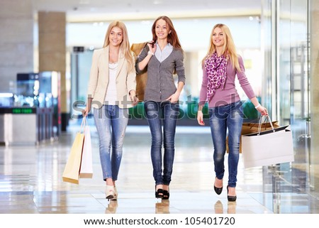 Smiling girls with shopping bags walking in the store