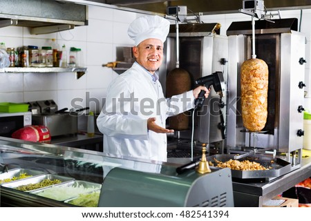 Smiling glad mature man cook cutting kebab meat on kitchen in fast food cafe