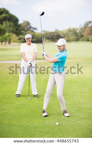 Smiling golfer woman taking shot while standing by man