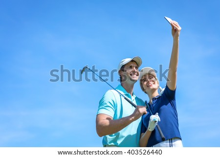 Smiling golfers making selfie outdoors
