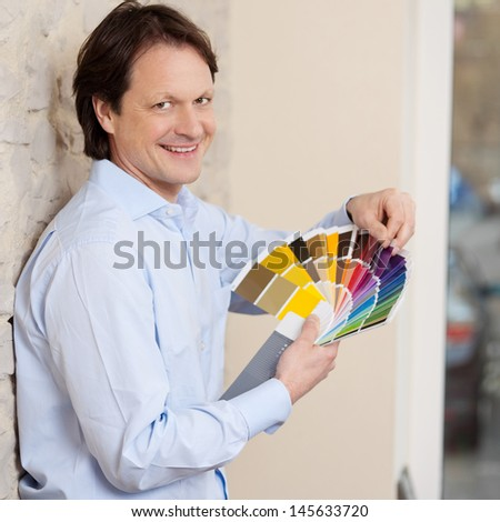 Smiling good looking man checking paint colours fort a wall against a colorful set of swatches held in his hand as he plans his renovations - stock photo