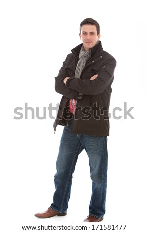 Smiling good-looking middle-aged man in casual winter fashion wearing jeans, a jacket and scarf standing in a relaxed pose with folded arms isolated on white