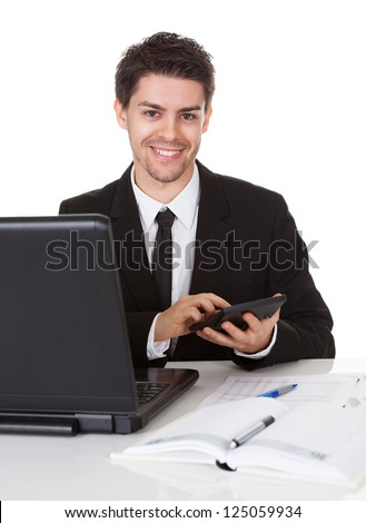 Smiling good looking young accountant sitting at his desk making calculations on a handheld calculator - stock photo
