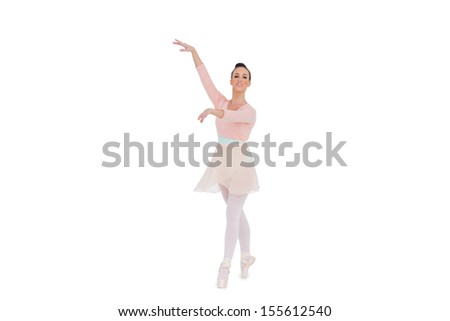 Smiling gorgeous ballerina with her arms up posing on white background  - stock photo