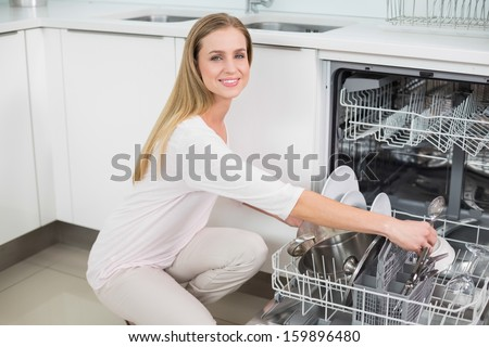 Smiling gorgeous model kneeling next to dish washer in bright kitchen - stock photo