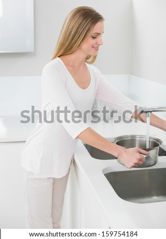 Smiling gorgeous woman filling pan with water in bright kitchen