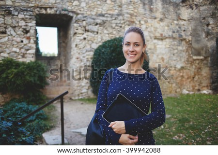 Smiling gorgeous woman tourist with portable digital tablet in hands and rucksack on back is posing for photos on the memory during excursion, while standing against the wall of historical old castle - stock photo