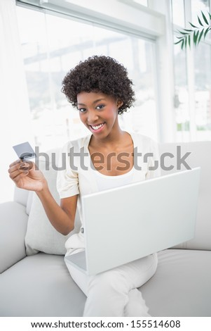 Smiling gorgeous woman using her credit card to buy online sitting on cosy sofa