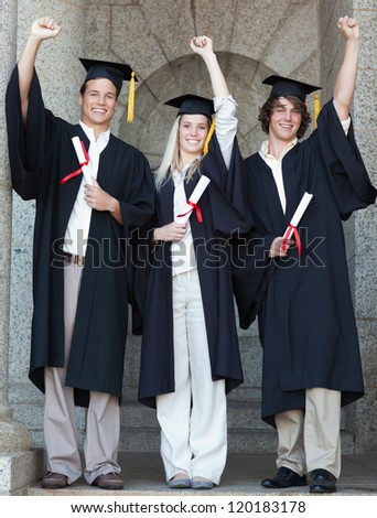 Smiling graduates raising arm with university in backgroung - stock photo