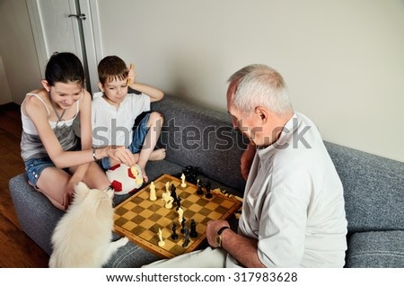 smiling grandchildren with grandpa playing chess and looking at the dog horizontal - stock photo