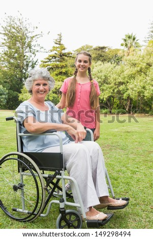 Smiling granddaughter with grandmother in her wheelchair looking at camera in the park - stock photo
