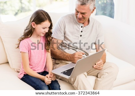 Smiling grandfather and granddaughter using laptop on the sofa