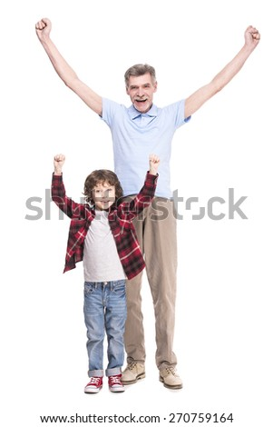 Smiling grandfather and his cute grandson raised arms up are standing on a white background.