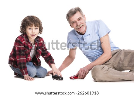 Smiling grandfather and his grandson are playing with cars, over the white background.