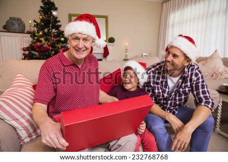 Smiling grandfather opening his gift at home in the living room - stock photo