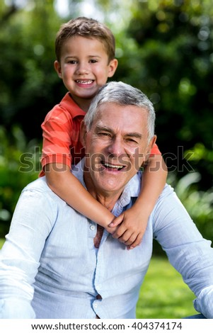 Smiling grandfather with grandson sitting in yard - stock photo