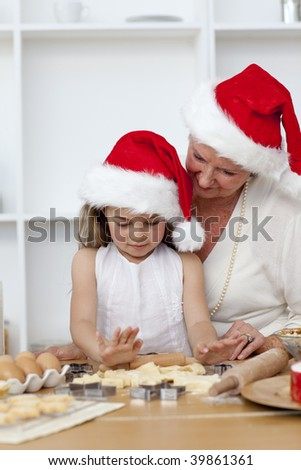 Smiling grandmother and little girl baking Christmas cakes in the kitchen - stock photo