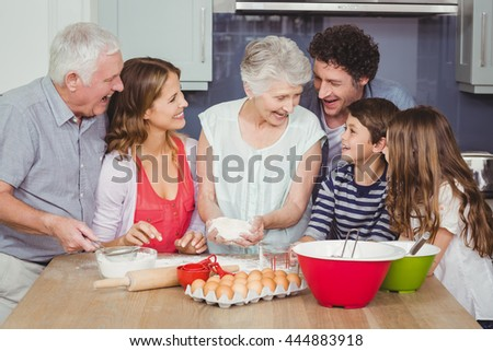 Smiling grandmother cooking food with family in kitchen at home - stock photo