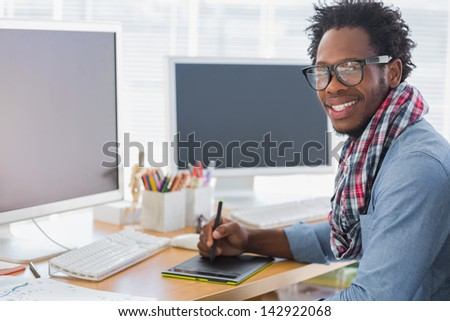 Smiling graphic designer using a graphics tablet in a modern office - stock photo