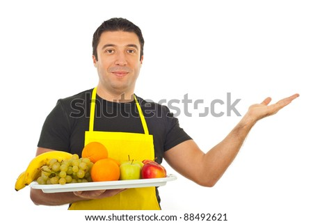 Smiling greengrocer holding plateau with fruits and making presentation to right part of image isolated on white background - stock photo