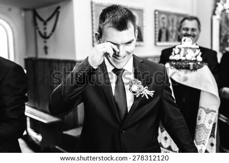 smiling groom in suit crying in church