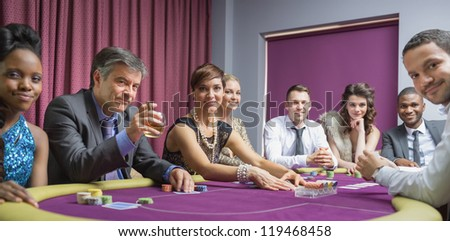 Smiling group at poker table in casino - stock photo