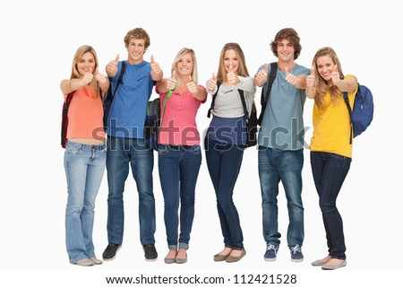 Smiling group looking at the camera while giving a thumbs up as they wear backpacks - stock photo