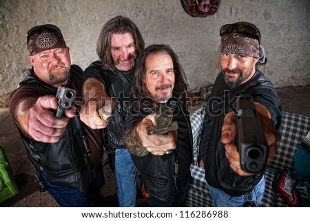 Smiling group of Caucasian bikers in leather jackets with weapons