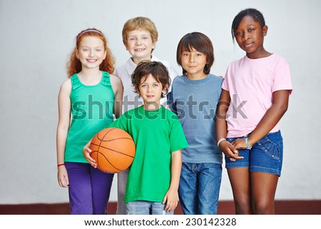 Smiling group of children in elementary school with basketball - stock photo