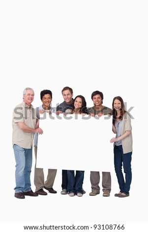 Smiling group of friends holding blank sign together against a white background - stock photo