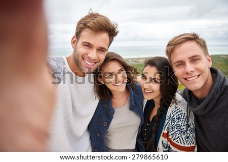 Smiling group of friends posing for a selfie while standing together outdoors - stock photo
