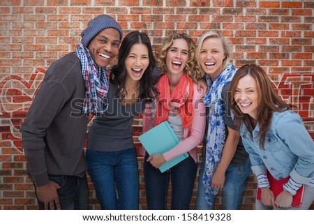 Smiling group of friends posing together on brick background - stock photo