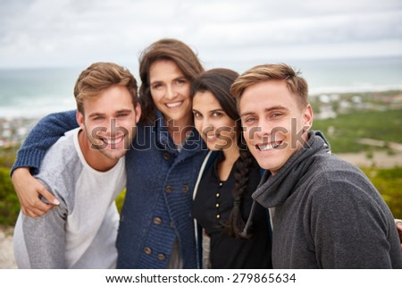Smiling group of friends standing outdoors on a nature trail posing for a picture - stock photo