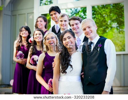 Smiling group of multiethnic wedding party together outside - stock photo