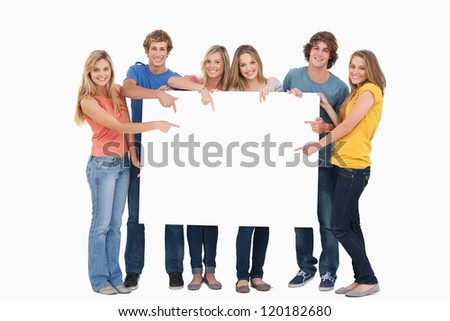 Smiling group of people with a blank space as they point to it and look at the camera - stock photo