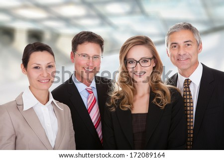 Smiling group of stylish business professionals standing in a row with their arms folded looking at the camera