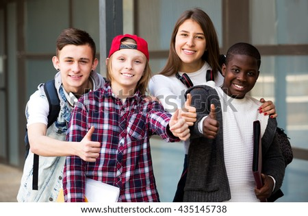 Smiling group of teens posing outside school with papers for study - stock photo