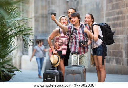 Smiling group of travelers with luggage doing selfie at the street - stock photo