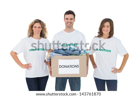 Smiling group of volunteers holding donation box on white background - stock photo
