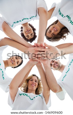 Smiling group of volunteers piling up their hands on white background - stock photo