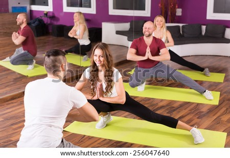 Smiling group of young adults having fitness class - stock photo