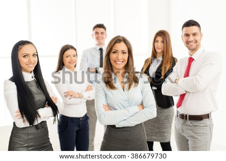 Smiling group of young business people standing with arms crossed and looking at camera.